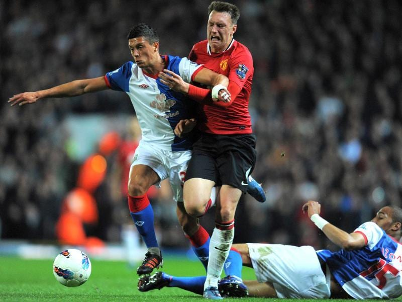 Manchester United defender Phil Jones (C) vies with Blackburn Rovers midfielders Jason Lowe (L) and Steven N'Zonzi during their English Premier League football match at Ewood Park, Blackburn, north-west England. AFP Photo/Andrew Yates