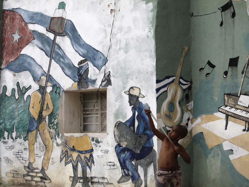 A boy plays with a catapult on a street beside a wall painted with a mural in Havana. Reuters photo/Desmond Boylan