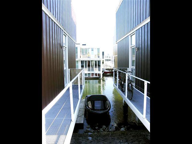 A boat floats between amphibious houses in the harbour of the IJburg neighborhood, in Amsterdam. AP Photo/Margriet Faber