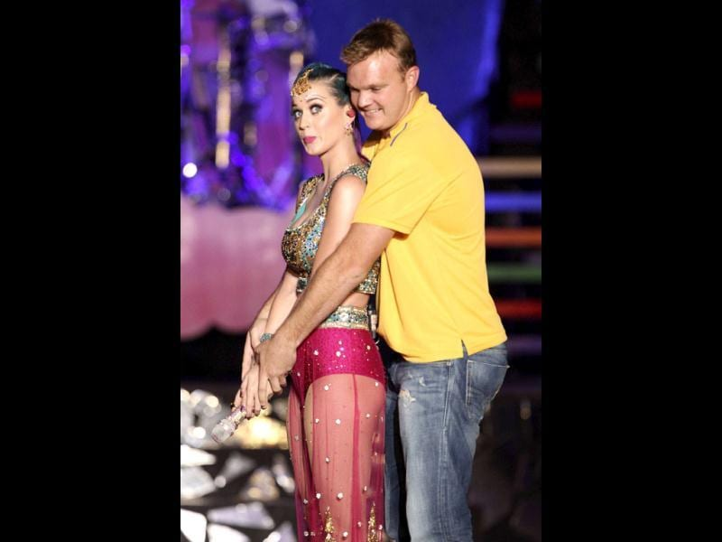 In this handout photograph provided by the Indian Premier League, US singer Katy Perry asks cricketer Doug Bollinger to show her how to bat during the IPL2012 opening function and concert held at the YMCA College of Physical Education Grounds, Nandanam, Chennai. AFP/Ron Gaunt