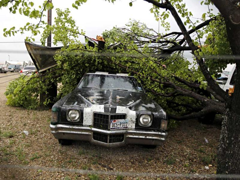 A downed tree lays on top of a parked car after a tornado tore through the southeastern portion of Dallas County near Lancaster, Pa. AP Photo/G.J. McCarthy