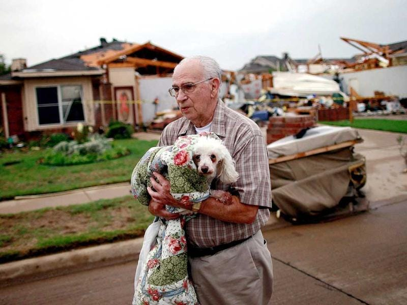 David Lowe carries his daughter's dog, Phoebe, after the dog was rescued from the rubble of a destroyed home in Arlington, Texas. AFP Photo/Tom Pennington.
