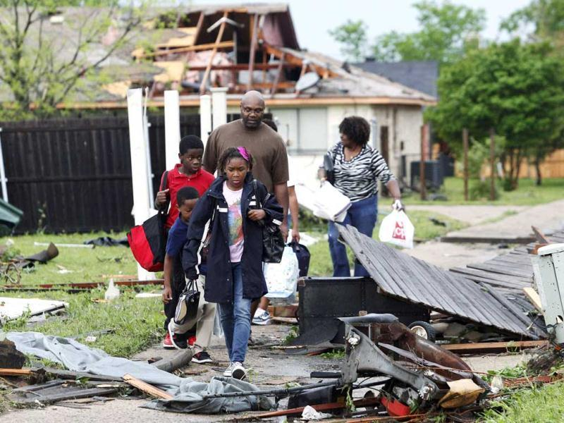 A family walks through the debris after their neighborhood was damaged by a series of tornadoes ripped through the Dallas suburb of Lancaster, Texas. Reuters/Tim Sharp
