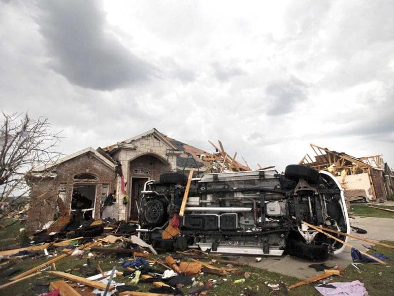 A vehicle sits toppled over in front of tornado damaged homes in Forney, Texas. AP Photo/Tony Gutierrez.