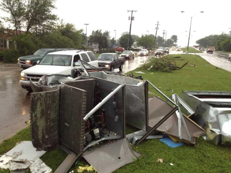 Debris scatter the street in southern Dallas County, Texas. Tornadoes tore through the Dallas area, peeling roofs off homes, tossing big-rig trucks into the air and leaving flattened tractor trailers strewn along highways and parking lots. AP Photo/Ron Ennis.