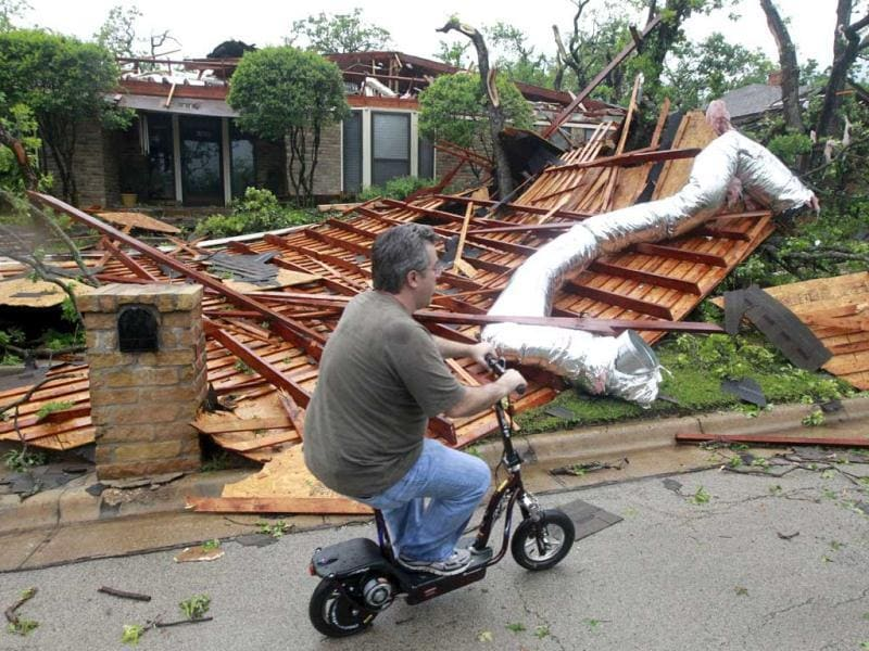 Sean Lanham inspects his neighborhood on a scooter after an apparent tornado hit near Bardin Road and and Spring Creek Road in Arlington, Texas. (AP Photo)