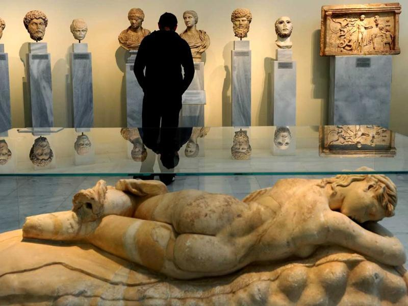 A visitor looks at antiques at the National Archeological museum in Athens. Faced with massive public debt as it moves into a fifth year of recession, Greece is finding that its fabled antiquity heritage is proving a growing burden. AFP Photo/Aris Messinis
