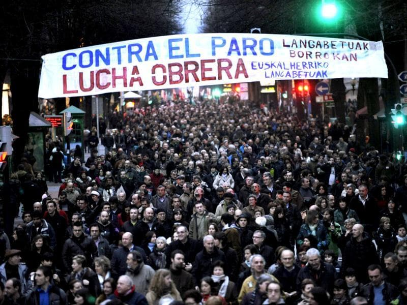 Demonstrators walk under a banner during a protest against cuts in Bilbao. Thousands marched through central Bilbao in protest against unemployment, recent labour reforms and cuts in public and social services. The banner reads