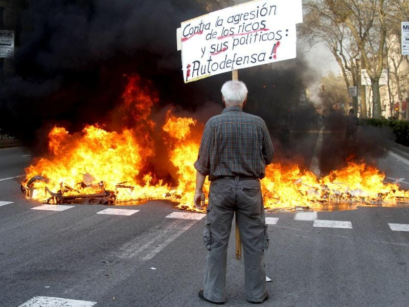 A demonstrator holds a banner in front of a fire started by anti-establishment groups during a general strike in central Barcelona. Spanish workers staged a general strike to protest against labour reforms which the government declared