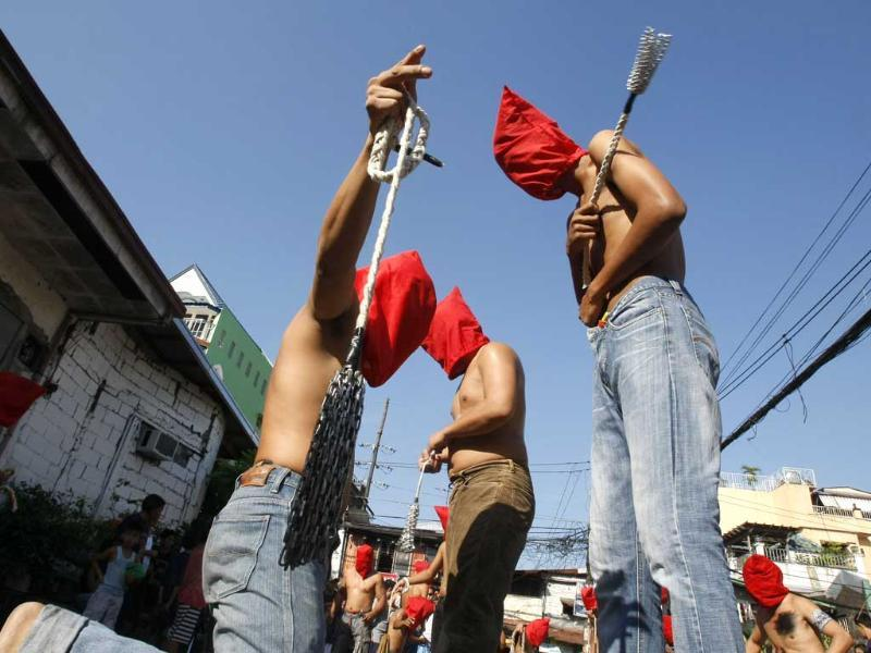 Hooded penitents flagellate themselves in a ritual to atone for their sins in observance of Holy Week at Mandaluyong city, east of Manila, Philippines. AP Photo/Bullit Marquez