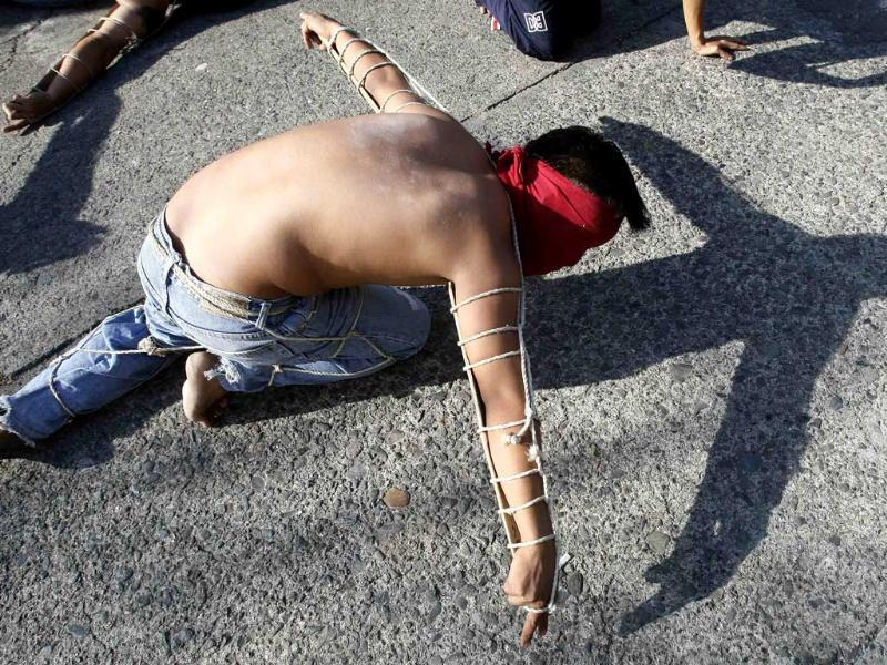 A hooded penitent lay prone on the pavement during flagellation ritual to atone for their sins in observance of Holy Week at Mandaluyong city, east of Manila, Philippines. AP Photo/Bullit Marquez