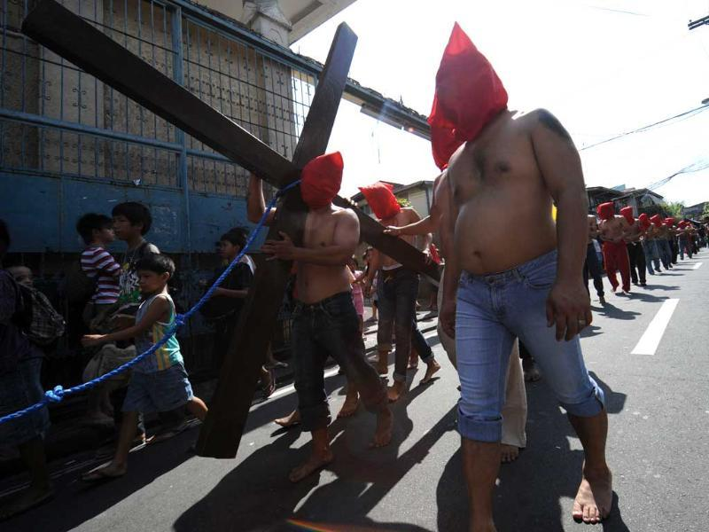 A penitent walking barefoot carries a cross while others flagellates themselves as part of Lenten observance in Manila. AFP Photo/Ted Aljibe