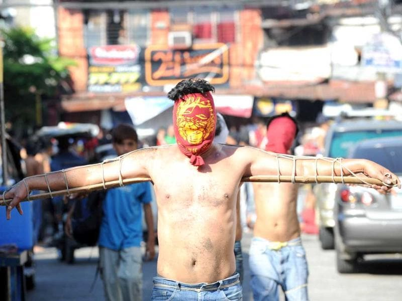 Penitents with their hands tied to a bamboo pole walk through the streets as part of Lenten observance in Manila. AFP Photo/Ted Aljibe.