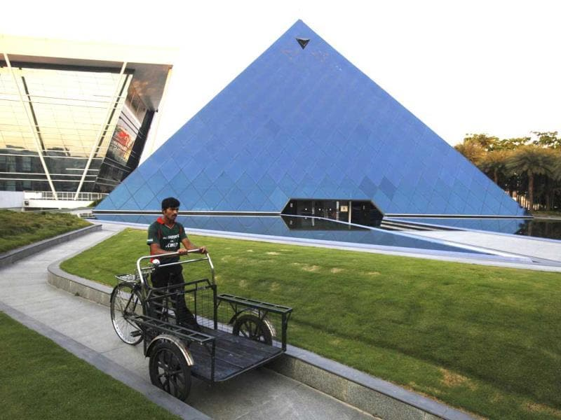 A man pushing a tricycle cart walks in front of a pyramid-shaped building made out of glass in the Infosys campus at Electronics City in Bangalore. India's IT industry, with Bangalore firms forming the largest component, is now worth an annual $100 billion and growing 14 percent per year. (Reuters)