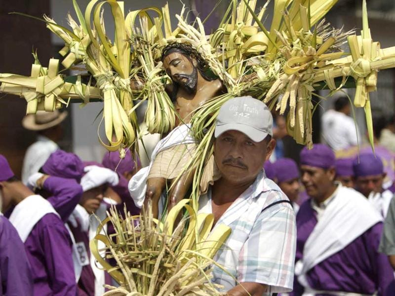 A man carrying a statue of Jesus Christ participates in a Holy Week procession in Izalco, some 40 miles west of San Salvador, El Salvador. (AP Photo/Luis Romero)