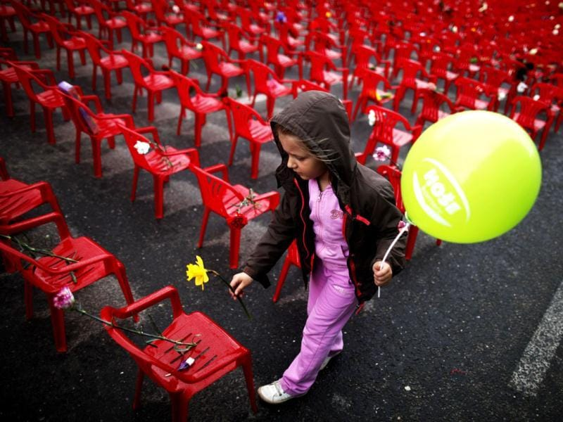 A child puts flowers on one of the 11,541 red chairs along Titova street in Sarajevo, as the city marks the 20th anniversary of the start of the Bosnian war. Reuters photo/Dado Ruvic