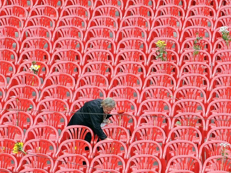 An elderly woman leaves a flower on some of 11,451 empty chairs on the main street of Sarajevo. More than 11,000 red chairs, symbolizing 11541 victim of the siege, lined Sarajevo's main avenue as Bosnians marked the 20th anniversary of the bloodiest conflict in Europe since World War II with songs and remembrance. AFP Photo/Elvis Barukcic