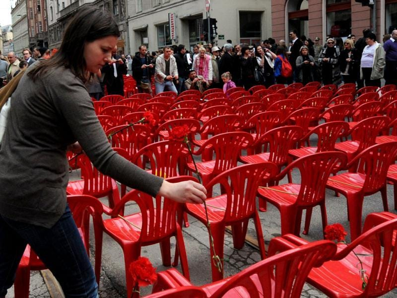 A Bosnian woman leaves a flower on one of 11,451 empty chairs on the main street of Sarajevo. More than 11,000 red chairs, symbolizing 11541 victim of the siege, lined Sarajevo's main avenue as Bosnians marked the 20th anniversary of the bloodiest conflict in Europe since World War II. AFP Photo/Elvis Barukcic