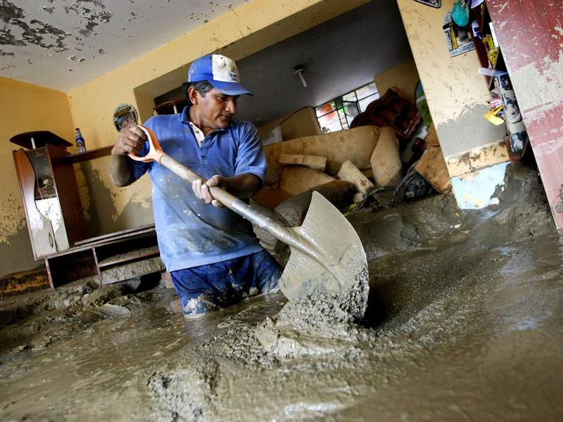 A man shovels mud out of his house after a landslide in Chosica Peru. A state of emergency has been declared by Peru's government in several towns of the Amazonian region where buildings were affected by landslides and flooding caused by heavy rains. AP Photo