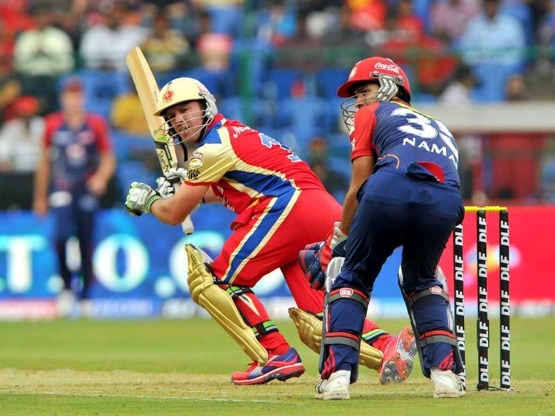 Royal Challengers Bangalore batsman AB de Villiers (C) is watched by Delhi Daredevils wicketkeeper Naman Ojha as he plays a stroke during the IPL Twenty20 cricket match at the M Chinnaswamy Stadium in Bangalore. AFP Photo/Manjunath Kiran