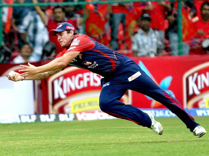 Delhi Daredevils Doug Bracewell dives to complete a catch of Andrew McDonald of Royal Challengers Bangalore during their IPL 5 match in Bangalore. (PTI Photo/Shailendra Bhojak)