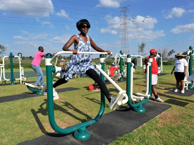 People work out at new outdoor gym in Soweto. Opened by the Johannesburg city council a month ago, the gym has seen the people of all ages pumping iron and swaying around in swing-like contraptions designed to target problem fat. AFP