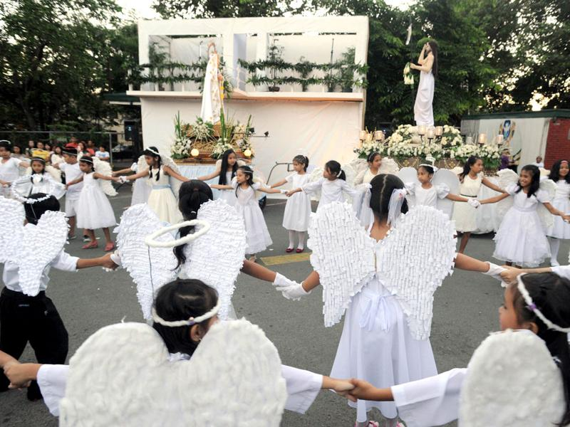 Philippine schoolchildren dressed as angels dance as they take part in a religious procession outside a Catholic church in Quezon City suburban Manila. AFP/Jay Directo