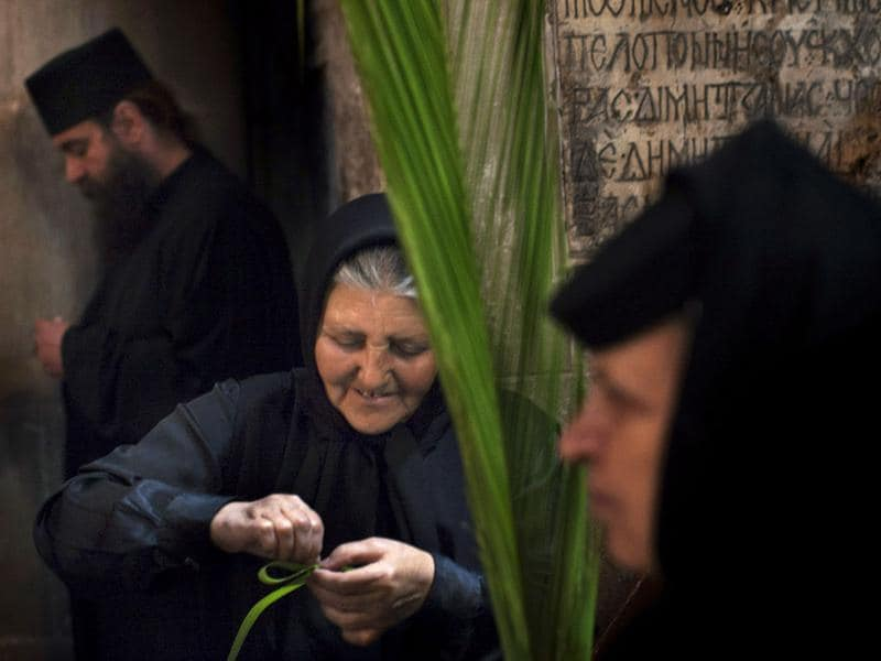 A Greek Orthodox nun makes a palm ribbon before attending a vesper ceremony inside the Church of the Holy Sepulchre, traditionally believed to be the burial site of Jesus Christ, in Jerusalem's Old City. AP Photo/Bernat Armangue