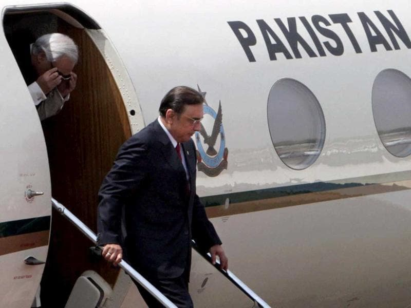 Pakistan President Asif Ali Zardari with the country's high commissioner to India Shahid Malik disembarks as they arrive at AFS Palam in New Delhi. PTI Photo/Kamal Singh