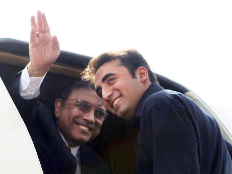Pakistan President Asif Ali Zardari waves from his plane as he along with his son and Pakistan People's Party chief Bilawal Bhutto Zardari prepares to leave for Jaipur from AFS Palam in New Delhi. PTI Photo by Subhav Shukla