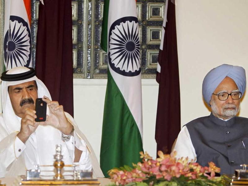 Emir of Qatar, Sheikh Hamad bin Khalifa Al Thani uses his phone to take video of the signing of agreements between India and Qatar as he sits next to Prime Minister Manmohan Singh at Hyderabad House in New Delhi. AP/Mustafa Quraishi