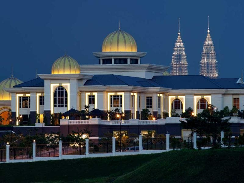 This photograph shows Malaysia's new National Palace during sunset with the Malaysian landmark Petronas Twin Towers in the background, in downtown Kuala Lumpur. Recalling the pageantry of Malay sultanates centuries ago, Malaysia installed its 14th king in a solemn ceremony, who pledged to protect Islam and maintain peace in the nation.Malaysia's unique revolving monarchy was passed to the sultan of Kedah state, Sultan Abdul Halim Mu'adzam Shah who previously served as the fifth Yang di-Pertuan Agong from 1970 to 1975 and become the first person to hold the position twice.  AFP PHOTO / Mohd RASFAN