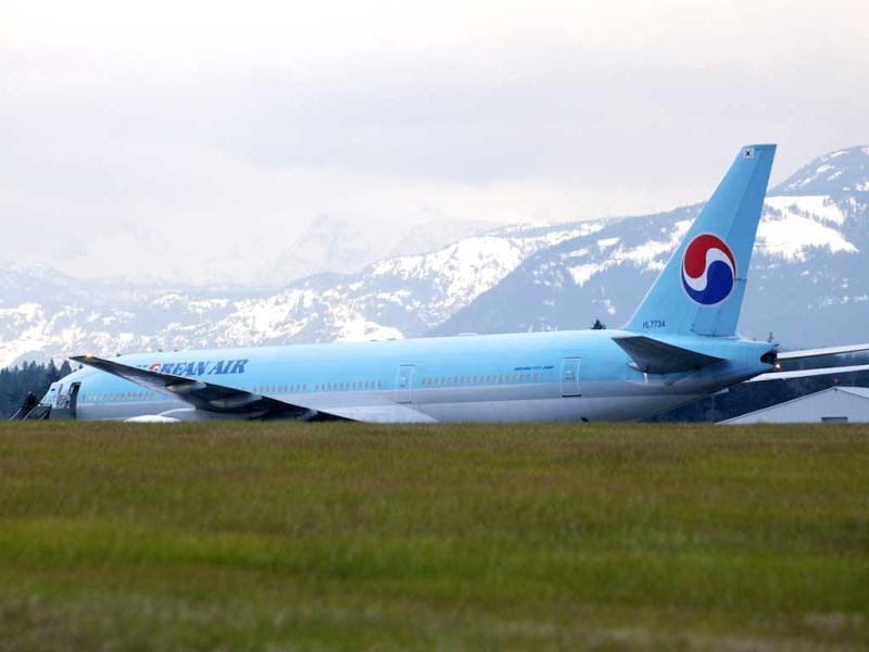 A Korean Air Boeing 777 is parked on the runway of a Canadian Forces base in Comox, British Columbia after an emergency landing. The plane, en route from Vancouver, British Columbia to Seoul, diverted to Comox on Vancouver Island under escort by two US fighter jets after the airline's US call center received a call about a threat on board. (AP Photo/The Canadian Press, Richard Warrington)