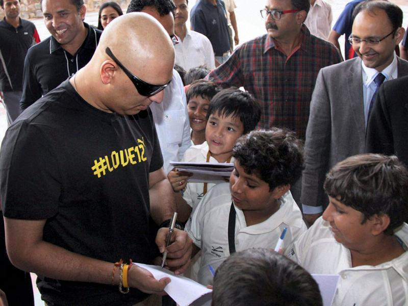 Cricketer Yuvraj Singh signs autograph for young fans after addressing a press conference in Gurgaon. (PTI Photo)