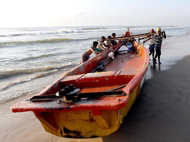 Fishermen move their boat to shore after fishing on Marina beach in Chennai. Reuters/Babu