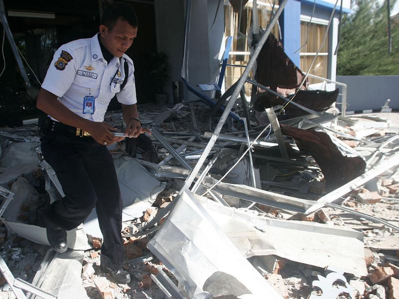 A security officer walks through debris from the strong earthquake at an office building in Banda Aceh, Sumatra island. AP/Heri Juanda