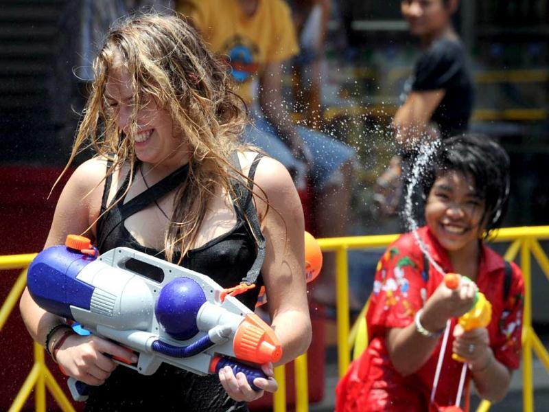 A Thai teenager squirts a tourist with water during the Songkran Festival along the famous travellers' area of Khao San Road in Bangkok. Songkran is the Thai New Year which starts on April 13 this year during which people celebrate by splashing water at each other. AFP PHOTO / PORNCHAI KITTIWONGSAKUL