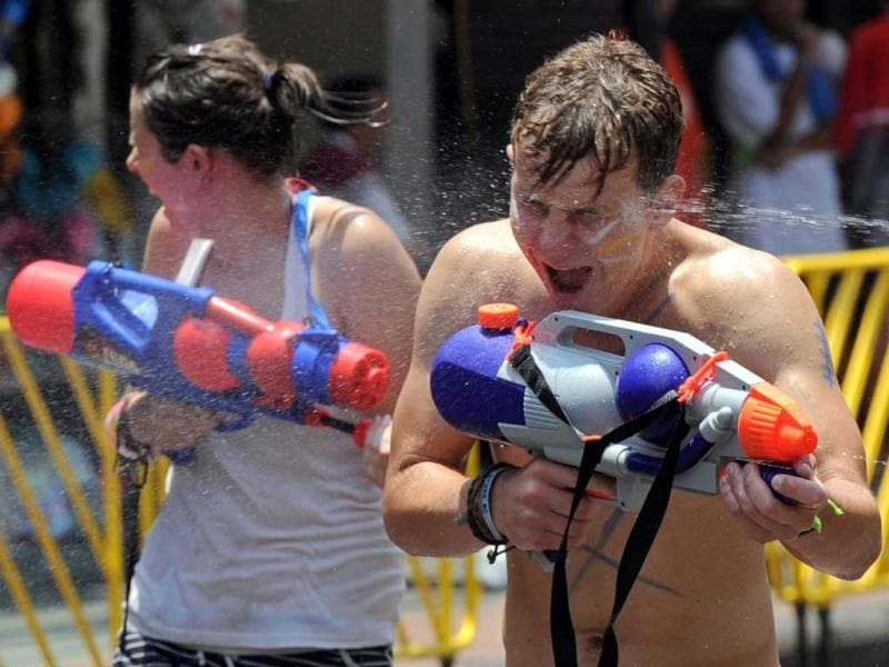 Tourists take part in watergun battles during the Songkran Festival along the famous travellers' area of Khao San Road in Bangkok. Songkran is the Thai New Year which starts on April 13 this year during which people celebrate by splashing water at each other. AFP PHOTO / PORNCHAI KITTIWONGSAKUL
