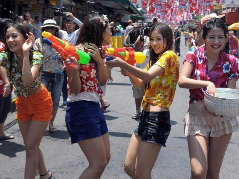 Thai teenagers enjoy a water battle with tourists during the Songkran Festival along the famous travellers' area of Khao San Road in Bangkok. Songkran is the Thai New Year which starts on April 13 this year during which people celebrate by splashing water at each other. AFP PHOTO / PORNCHAI KITTIWONGSAKUL