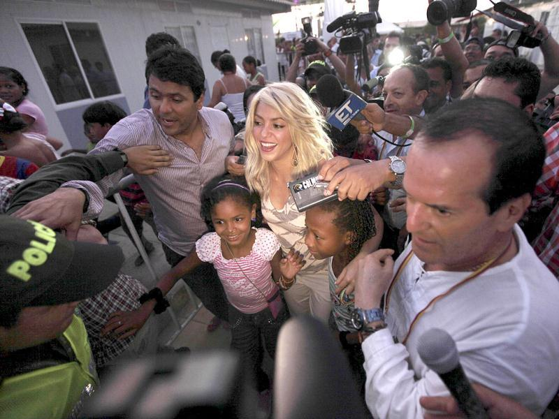 Surrounded by fans, Colombian singer Shakira, center, leaves after attending the inauguration of a child care center in Cartagena, Colombia. AP Photo/Fernando Llano