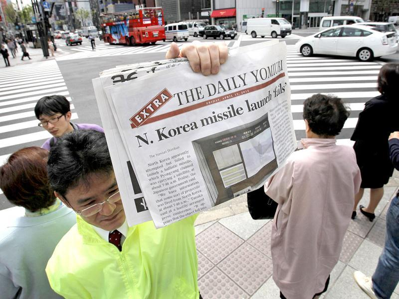 A newspaper employee shows an extra issue of the Daily Yomiuri reporting North Korea's rocket launch to hand over to passers-by in Tokyo. AP Photo/Itsuo Inouye