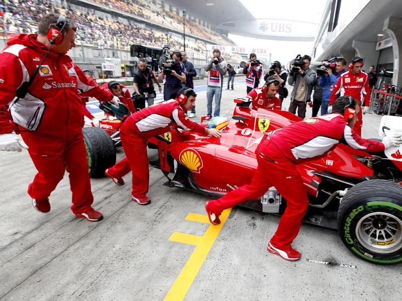 Ferrari mechanics push Fernando Alonso of Spain back into their team garage during practice for the Chinese Grand Prix in Shanghai, China. AP/Mark Baker