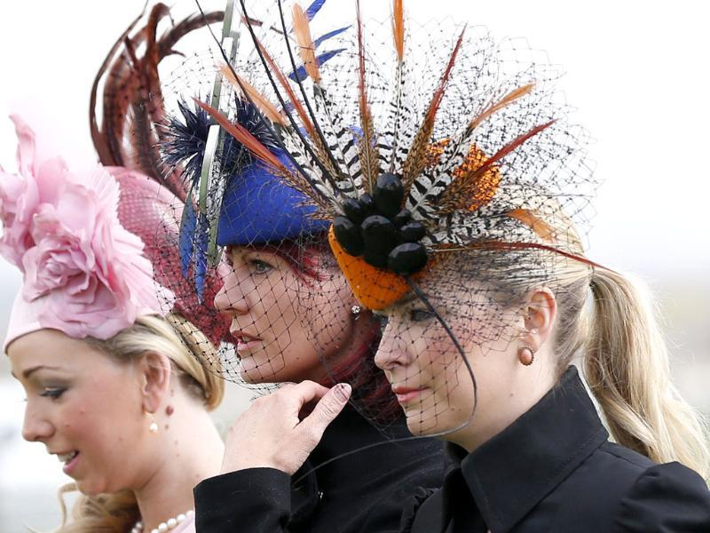 Women sport fancy headgears as they arrive for Ladies' Day on the second day of the Grand National meeting at Aintree in Liverpool, northern England. Reuters/Phil Noble