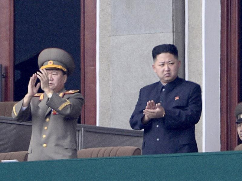 North Korean leader Kim Jong-Un (C) applauds during a official ceremony at a stadium in Pyongyang. AFP Photo/Pedro Ugarte