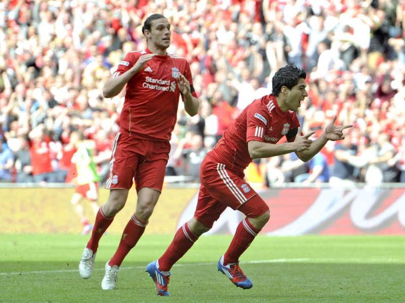 Liverpool's Luis Suarez (R) celebrates his goal against Everton with teammate Andy Carroll during their English FA Cup semifinal soccer match at Wembley Stadium in London. AP Photo/Tom Hevezi