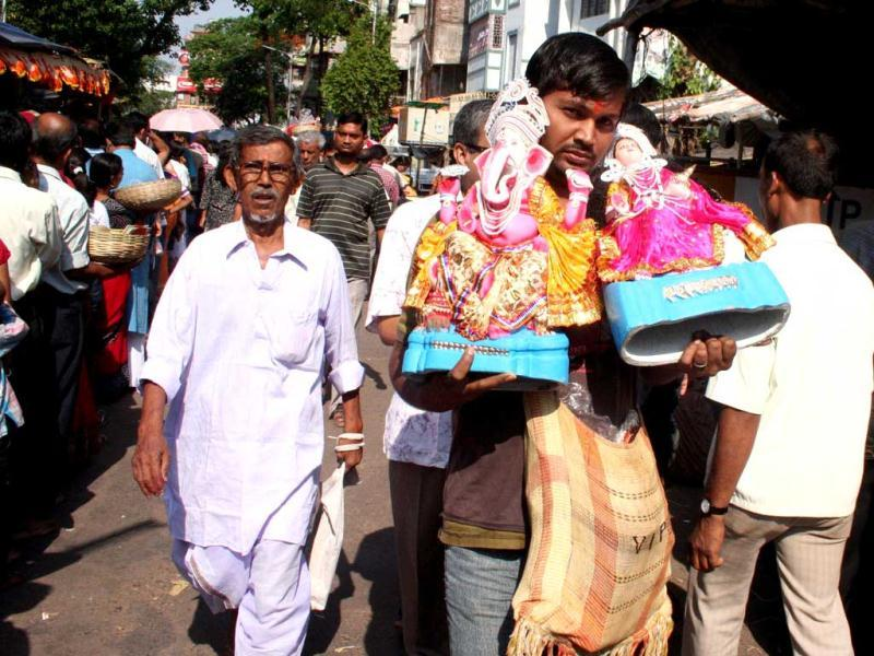 Devotees carry idols of Ganesha and Lakshmi for puja at Kalighat on the day of 'Poila Baisakh', Bengali New Year, 1419, in Kolkata.