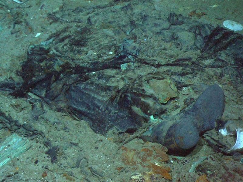 This photo shows the remains of a coat and boots, articulated in the mud on the sea bed near Titanic's stern, are suggestive evidence of where a victim of the disaster came to rest. (AP/Institute for Exploration)