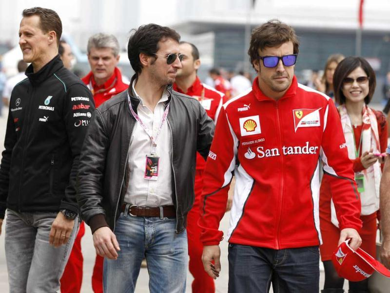Fernando Alonso of Spain and Michael Schumacher walk down the F1 paddock with fans as they arrive at the circuit for the Chinese Formula One Grand Prix in Shanghai. (AP Photo/Andy Wong)