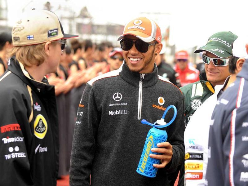 Lewis Hamilton chats to Lotus-Renault driver Kimi Raikkonen (L) and Caterham-Renault driver Heikki Kovalainen of Finland (R) as they head to the drivers parade before the start of the Chinese Grand Prix in Shanghai. (AFP Photo/Peter Parks)