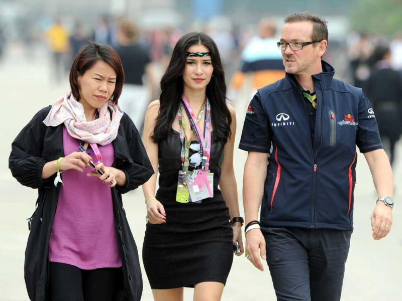 Celina Jade is escorted by a Red Bull team official in the paddock area before the start of the Chinese Grand Prix in Shanghai. AFP Photo